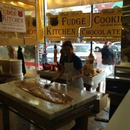 Chubs making maple fudge on a white marble table in the front of the fudge shop in downtown historic annapolis